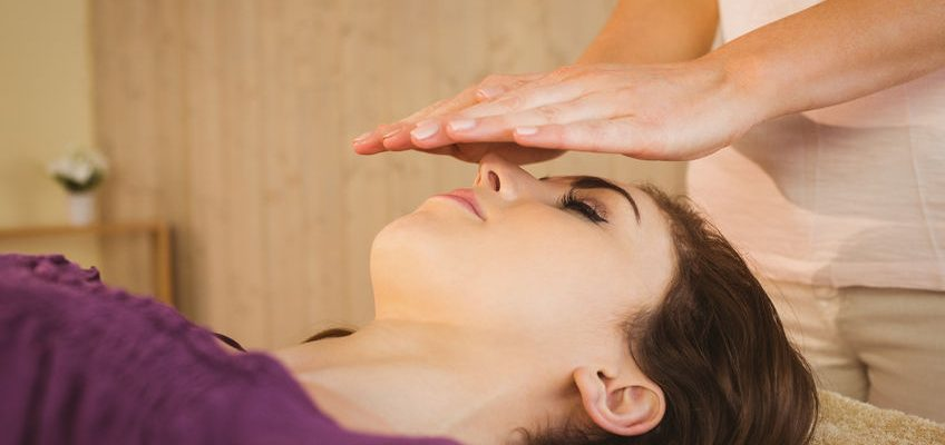 42396217 - young woman having a reiki treatment in therapy room