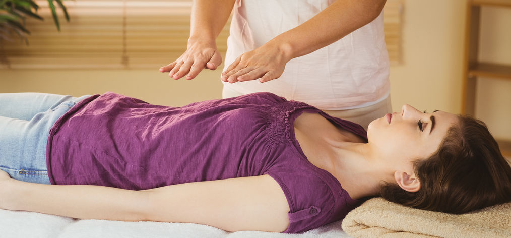42407604 - young woman having a reiki treatment in therapy room